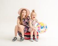 Le sorelle felici stanno sedendo su una valigia Fotografia Stock Libera da Diritti