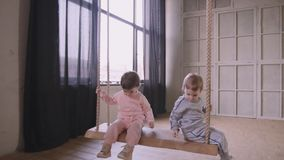 Le sorelle gemella il gioco che vanno in giro insieme la casa e che guidano su un'oscillazione stock footage