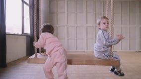 Le sorelle gemella il gioco che vanno in giro insieme la casa e che guidano su un'oscillazione archivi video