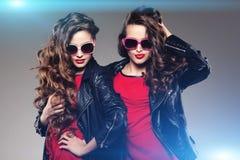 Le sorelle gemella in vetri di sole dei pantaloni a vita bassa che ridono due modelli di moda Fotografie Stock