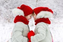 Le sorelle gemelli stanno toccando con le fronti e stanno tenendo un cuore in mani immagine stock