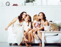 Le sorelle mature gemella a casa con la piccola figlia, famiglia felice che sorride vicino su, concetto reale moderno della gente Fotografie Stock