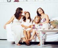 Le sorelle mature gemella a casa con la piccola figlia, famiglia felice nell'interno, concetto della gente di stile di vita Fotografia Stock