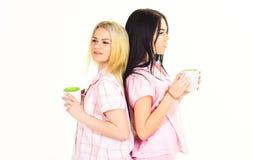 Le sorelle o i migliori amici in pigiami stanno indietro per appoggiare Biondo e castana sui fronti sonnolenti tiene le tazze con Fotografia Stock