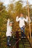 Le sorelle sciama sulle scale sul campo da giuoco Fotografia Stock
