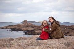 Le sorelle stanno sedendo sulla riva dell'oceano immagine stock