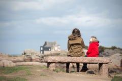 Le sorelle stanno sedendo sulla riva dell'oceano immagini stock