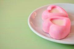 Le soufflé rose en forme de coeur durcit sur la table en bois verte Foyer mou sélectif sur le gâteau et le traitement en pastel Photo libre de droits