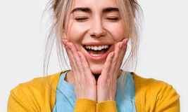 Le sourire étonné de jeune femme tient des joues à la main La femelle heureuse entend quelque chose agréable, garde des mains sur photos stock