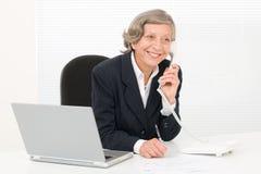 Le sourire aîné de femme d'affaires se reposent derrière le bureau Photo stock