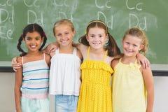 Le sourire badine la position avec le bras autour dans la salle de classe Photo libre de droits