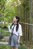 Le sourire chinois d'étudiante de lycée de l'Asie de belle beauté apprécient le jeu de temps gratuit dans le bambou de jardin de  image libre de droits