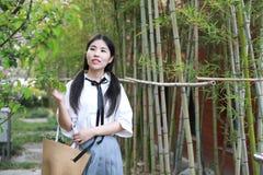 Le sourire chinois d'étudiante de lycée de l'Asie de belle beauté apprécient le jeu de temps gratuit dans le bambou de jardin de  photo libre de droits