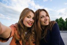 Le sourire de deux amies font Selfie Photographie stock