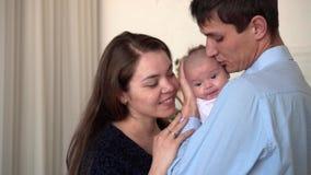 Le sourire de famille ? la maison, o? contact de p?re et de m?re, embrassent et embrassent leur petite fille banque de vidéos