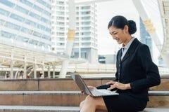 Le sourire de femme d'affaires et se reposent sur l'escalier et le mot de dactylographie dans l'ordinateur portable Photographie stock libre de droits