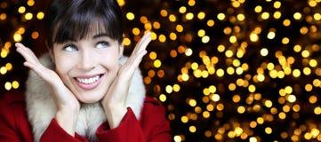 Le sourire de femme de Noël recherche à l'arrière-plan de lumières Photos stock