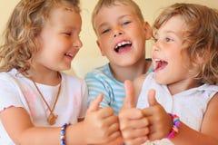 Le sourire des enfants trois affiche ensemble le geste en bon état Image libre de droits