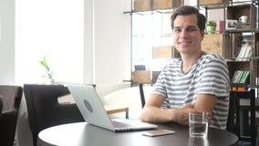 Le sourire heureux occasionnel détendent l'homme s'asseyant dans le bureau, regardant l'appareil-photo Images stock