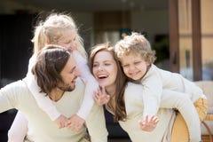 Le sourire heureux parents ferrouter le fils et la fille, leis de famille Photos libres de droits