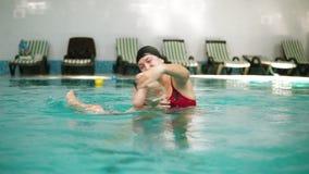 Le sourire heureux peu d'enfant nage ainsi que sa mère dans la piscine La jeune mère tourne et clips vidéos