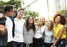 Le sourire jeunes des amis adultes heureux arme autour de l'épaule dehors Image stock