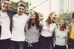 Le sourire jeunes des amis adultes heureux arme autour de l'épaule dehors Photographie stock libre de droits
