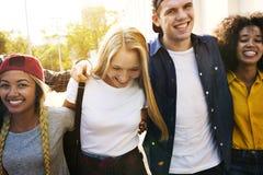 Le sourire jeunes des amis adultes heureux arme autour de l'épaule marchant dehors Photo stock