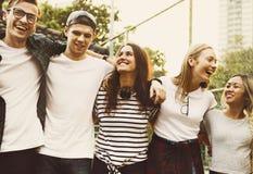 Le sourire jeunes des amis adultes heureux arme autour de l'amitié d'épaule dehors et du concept de connexion Images libres de droits