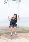 Le sourire mignon de fille et se reposent sur le siège d'oscillation photos libres de droits