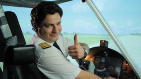 Le sourire pilote heureux à l'appareil-photo, pouces lèvent le signe, carrière réussie dans l'aviation banque de vidéos