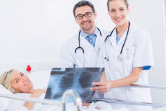 Le sourire soigne montrer le rayon X au patient féminin dans le lit photo stock