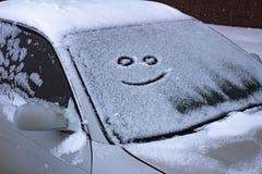 Le sourire triste et heureux sur le pare-brise neigeux d'une voiture photos libres de droits
