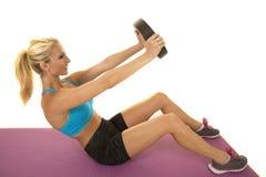 Le soutien-gorge blond de sports de bleu de femme alourdissent des genoux pliés photographie stock