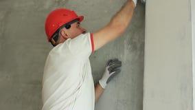 Le spécialiste aligne le mur dans la chambre Réparations dans la maison banque de vidéos