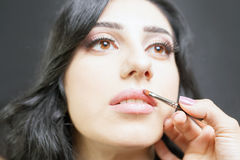 Le spécialiste dans le salon de beauté obtient le rouge à lèvres, lustre de lèvre, maquillage professionnel Images libres de droits