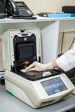 Le spécialiste du laboratoire place les échantillons dans un appareil spécial pour étudier la composition images libres de droits