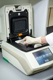 Le spécialiste du laboratoire place les échantillons dans un appareil spécial pour étudier la composition image libre de droits