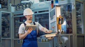 Le spécialiste masculin avec un ordinateur portable contrôle un panneau de commande banque de vidéos