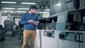 Le spécialiste masculin observe le processus fonctionnant d'une machine de développement de papier clips vidéos