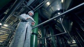 Le spécialiste masculin se tient dans une installation de distillerie et actionne un comprimé à partir de la vue du côté incliné banque de vidéos