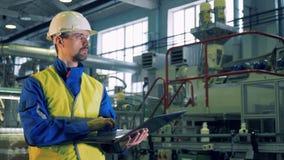 Le spécialiste masculin travaille sur un ordinateur portable dans une installation d'une usine en plastique clips vidéos