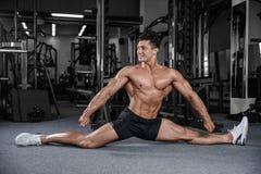 Le spaccature allunga l'uomo che allunga le gambe nella forma fisica bella della palestra Fotografia Stock Libera da Diritti