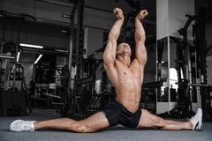 Le spaccature allunga l'uomo che allunga le gambe nella forma fisica bella della palestra Immagine Stock