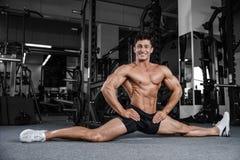 Le spaccature allunga l'uomo che allunga le gambe nella forma fisica bella della palestra Fotografie Stock