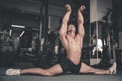Le spaccature allunga l'uomo che allunga le gambe nella forma fisica bella della palestra Immagine Stock Libera da Diritti