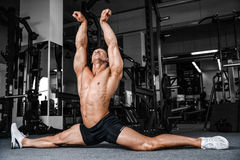 Le spaccature allunga l'uomo che allunga le gambe nella forma fisica bella della palestra Immagini Stock Libere da Diritti