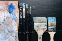 Le spazzole artistiche e una tavolozza si trovano su una tavola Fotografie Stock