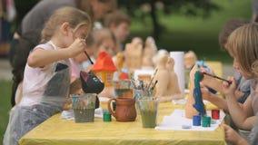 Le spazzole di pittura dei bambini su argilla calcola all'aperto stock footage