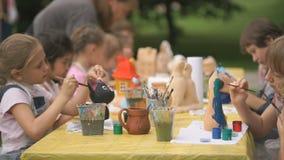 Le spazzole di pittura dei bambini su argilla calcola all'aperto video d archivio